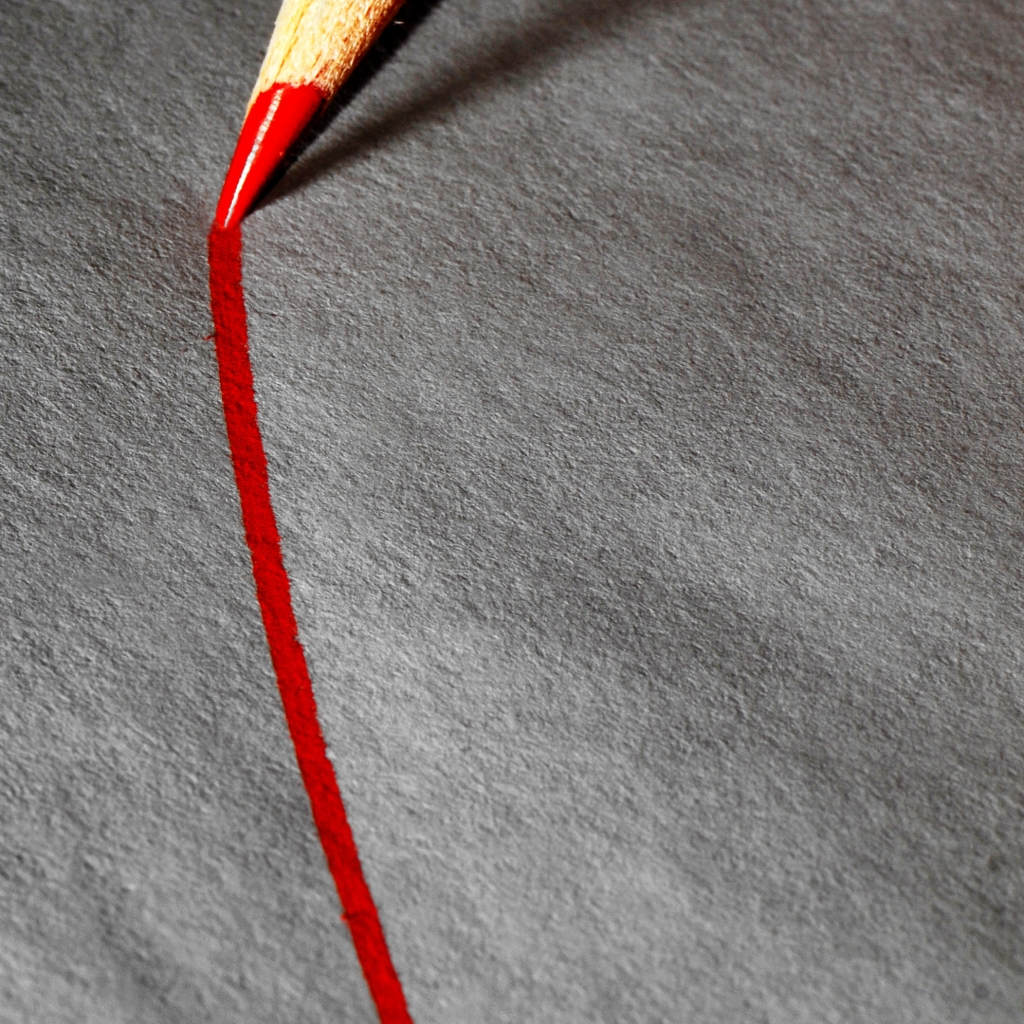 picture of a red color pencil drawing a curved line on a gray piece of paper