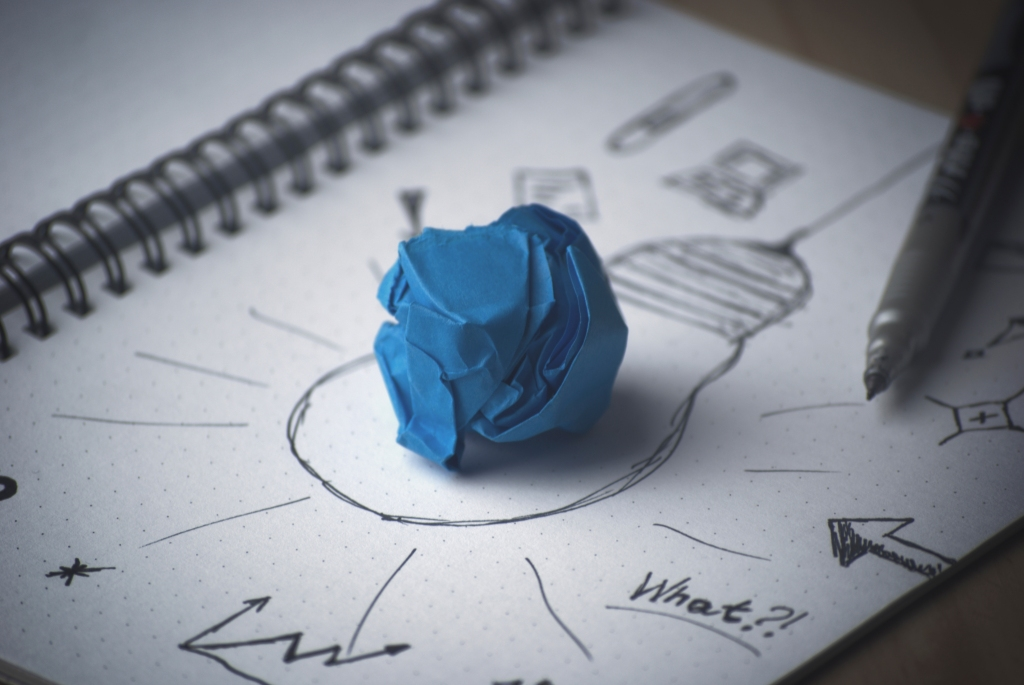 A notepad with a drawing of a light bulb and a blue crumpled piece of paper in the middle of the page