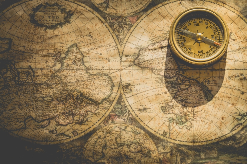 An old map of the world with a golden compass sitting on top of the map