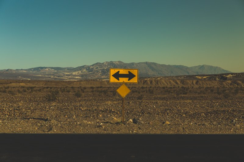 Highway with mountains in background. In foreground is a road sign with an arrow going left and right