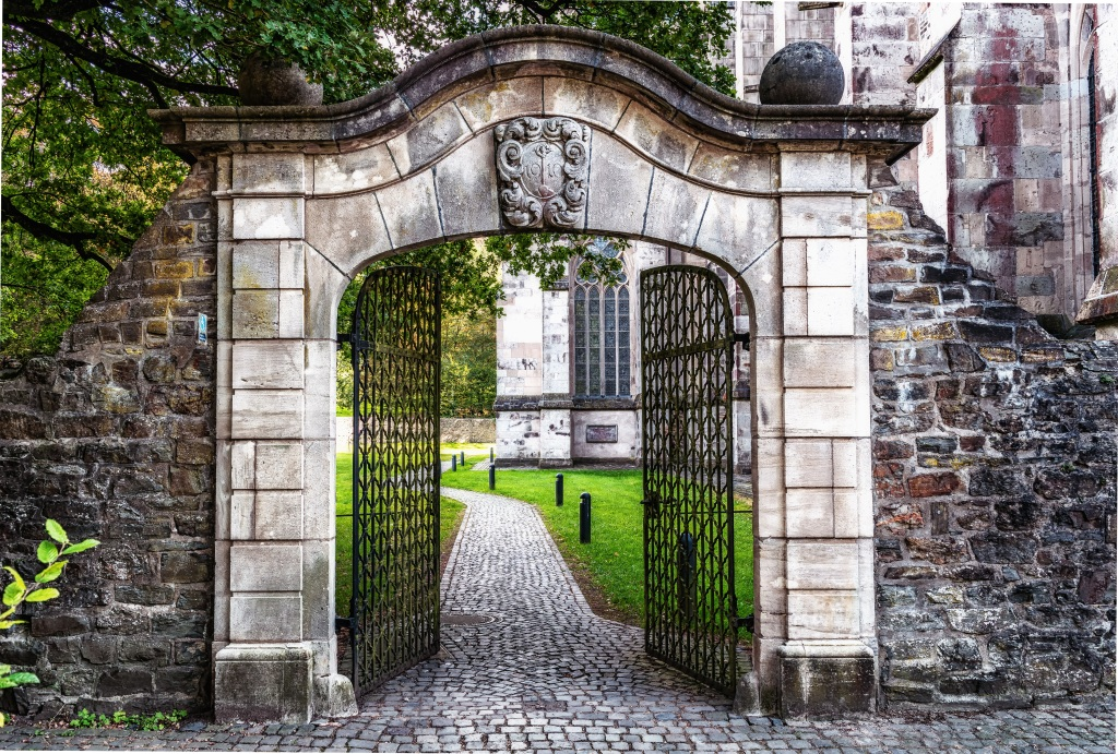 Image of an old gate made of bricks, with the door open to a cobblestone path and green lawn