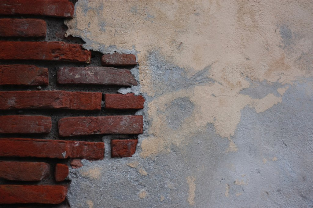 Brick wall, mostly covered in plaster
