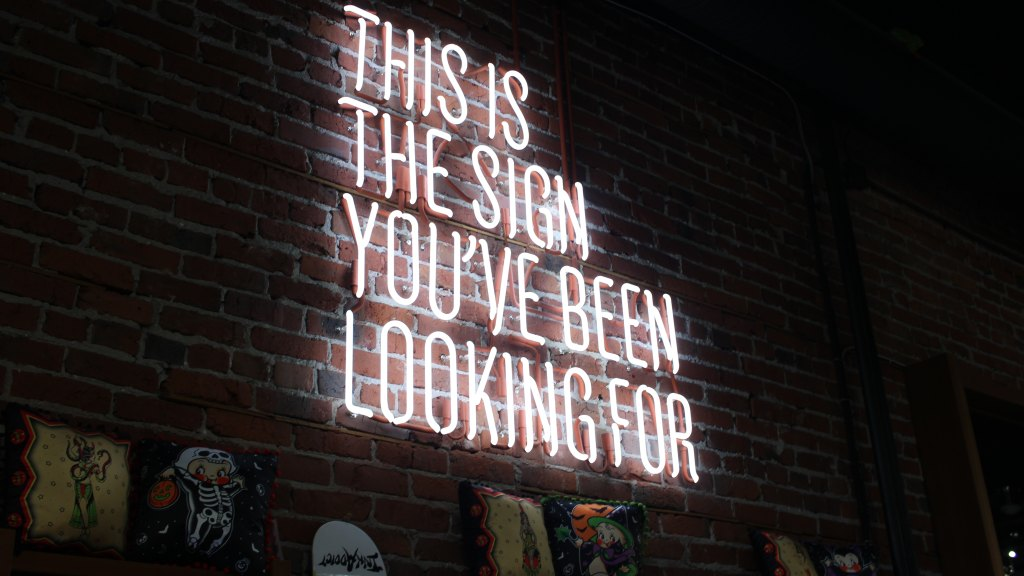 "An image of a neon sign on a brick wall that says, ""This is the sign you've been looking for"""
