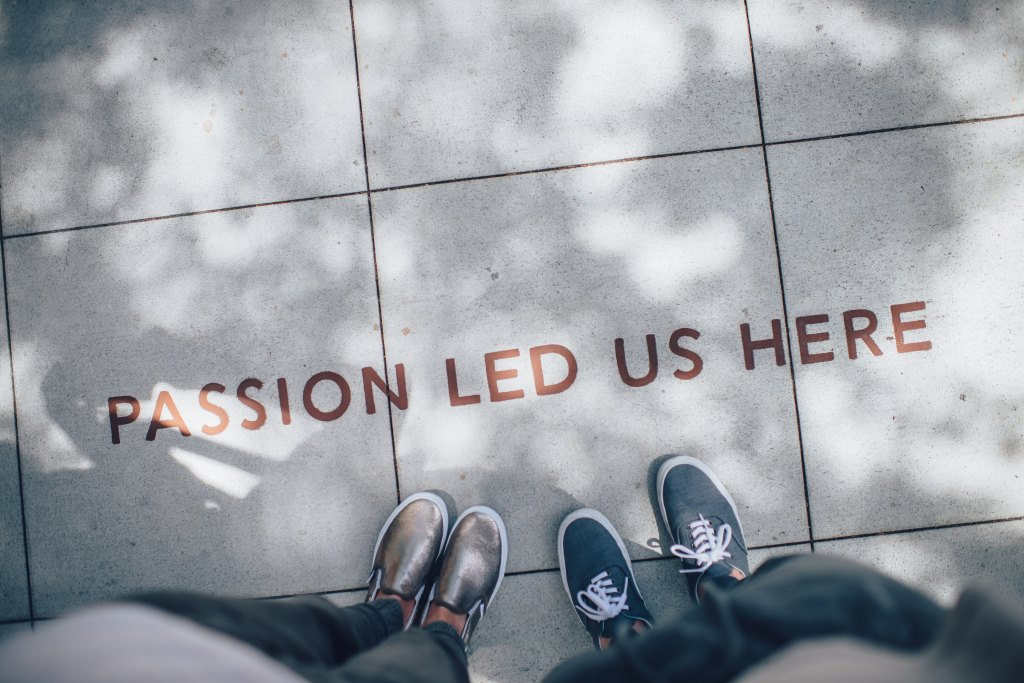 "A photograph with two pairs of shoes and the text on the sidewalk that says ""Passion led us here"""