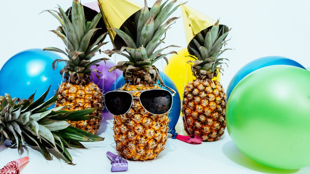 A picture of three pineapples wearing birthday hats and balloons are around them