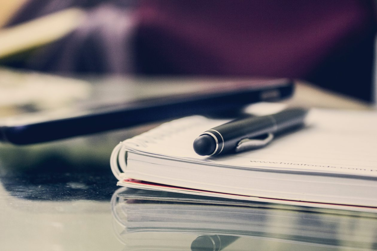 A picture of a table with a notebook and pen