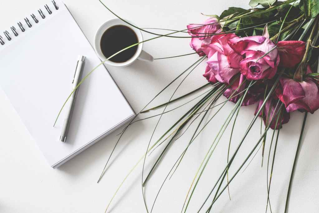 A photo of a table with a blank notebook, a cup of coffee, and a bouquet of pink flowers