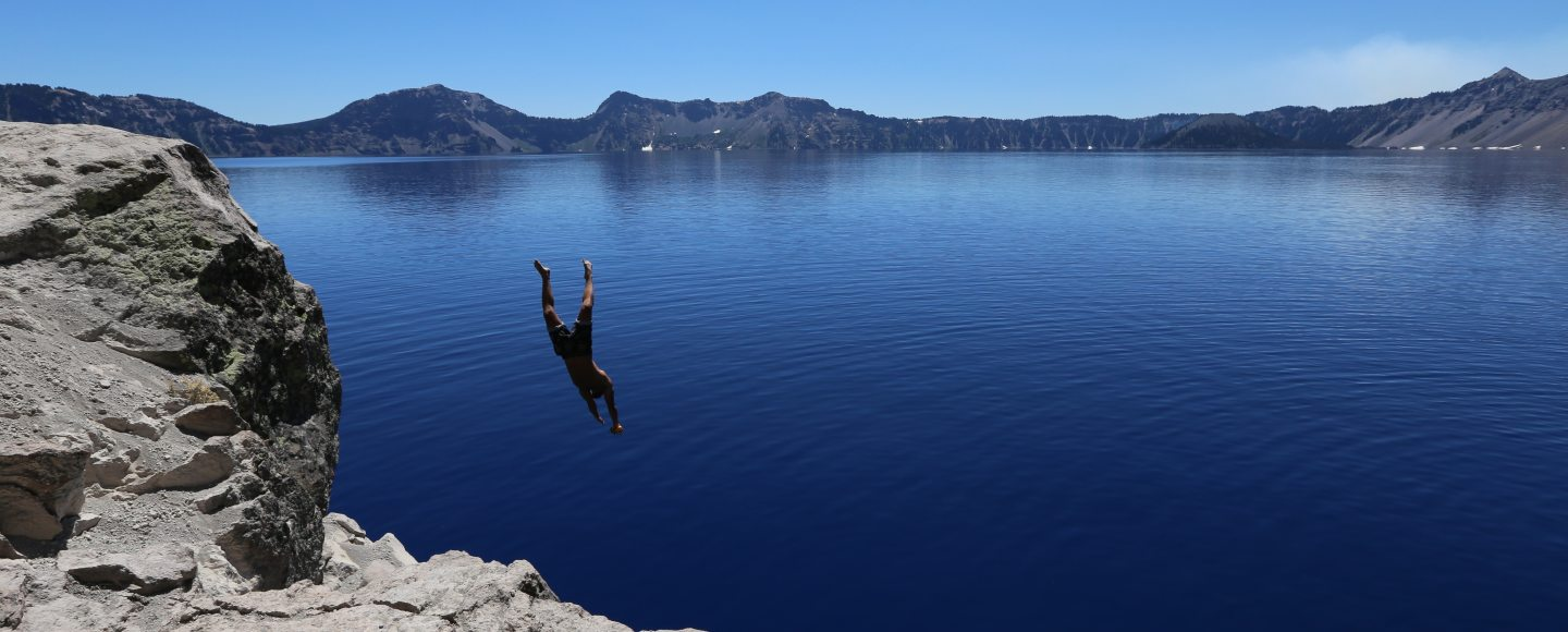 A picture of a large lake with someone jumping into the water