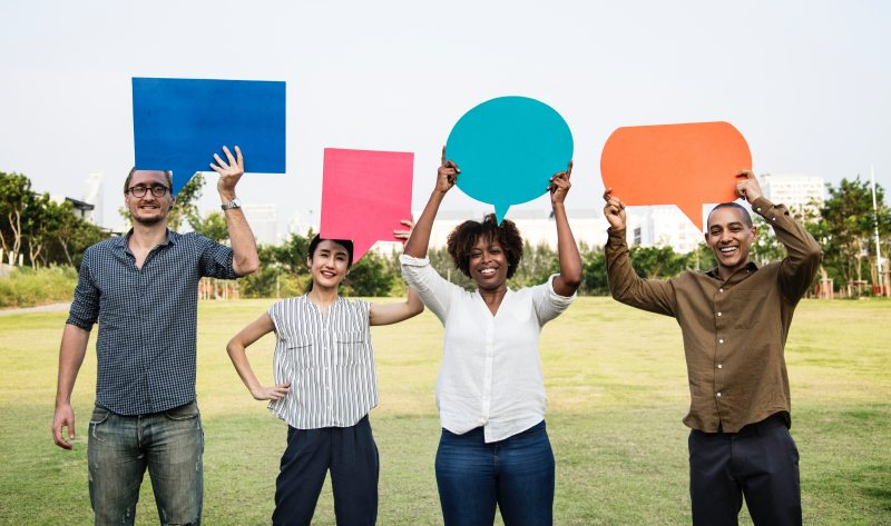 Picture of four people standing outside holding colored pieces of paper in the form of speech bubbles
