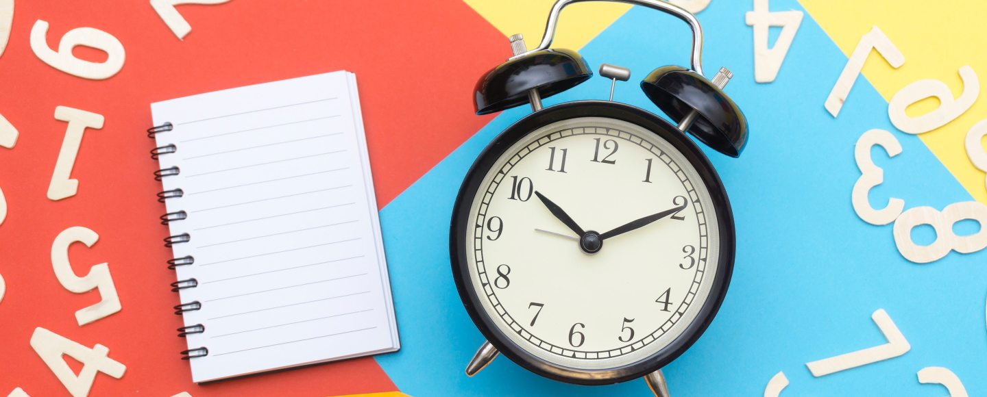An analog alarm clock sitting on colored pieces of paper next to a blank notebook