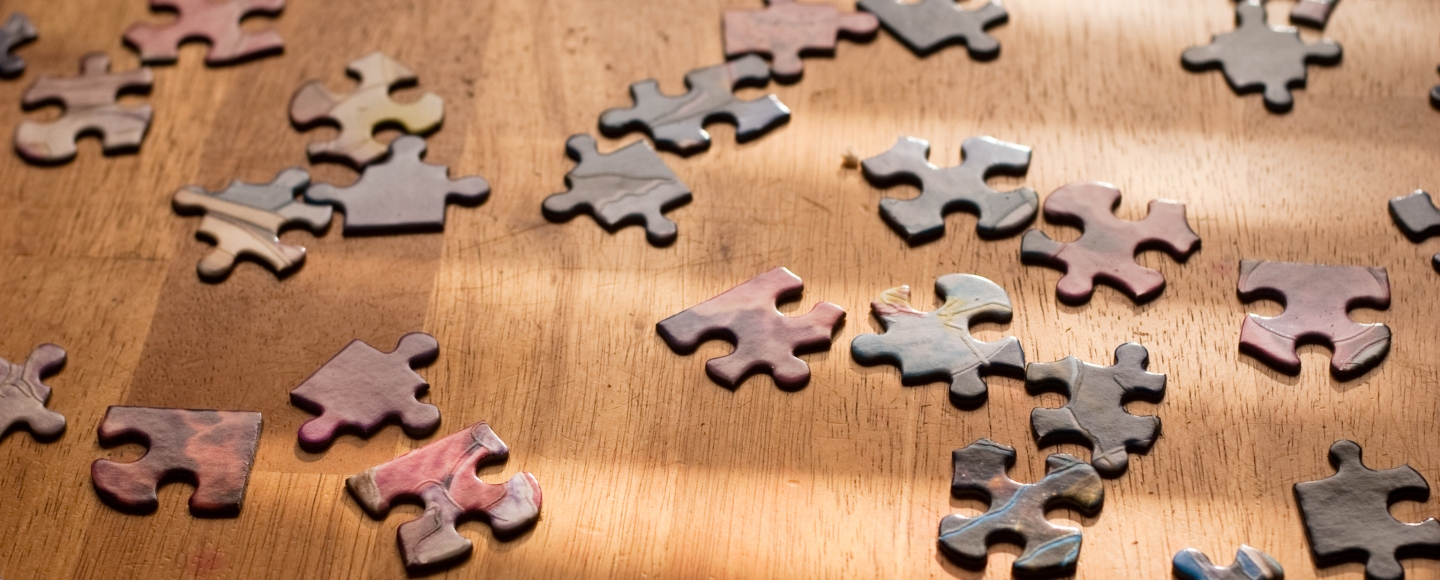 Picture of puzzle pieces on a wood table, scattered with no order to them
