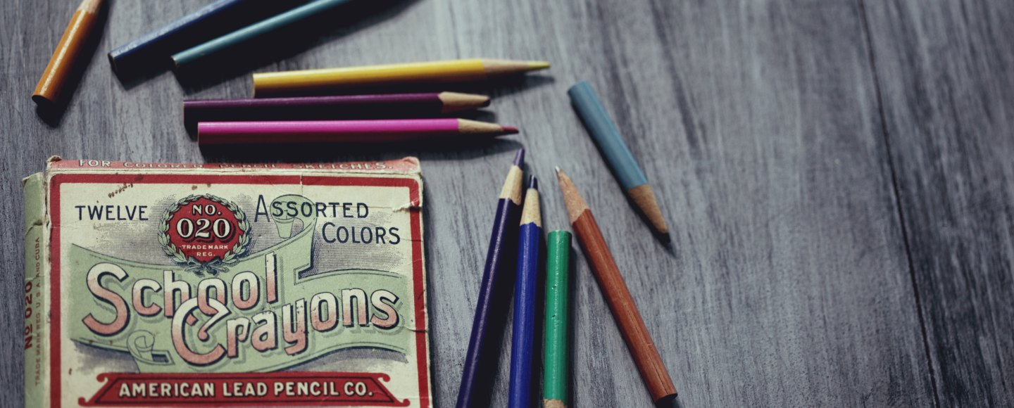 A table with an assorted box of school crayons
