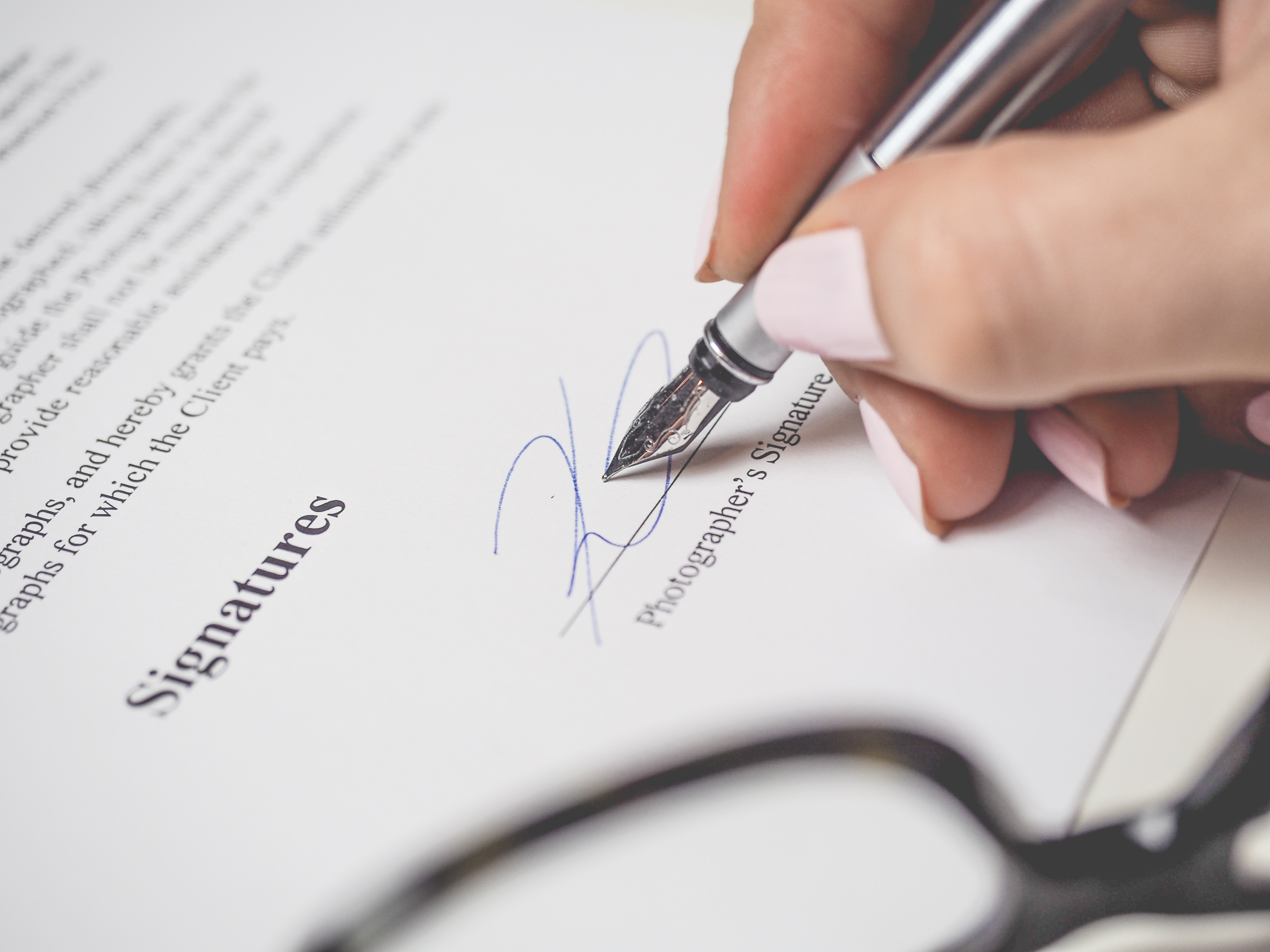 A close up of a person signing a contract