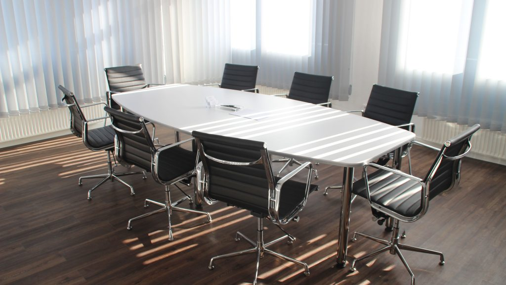 Empty white conference table with chairs