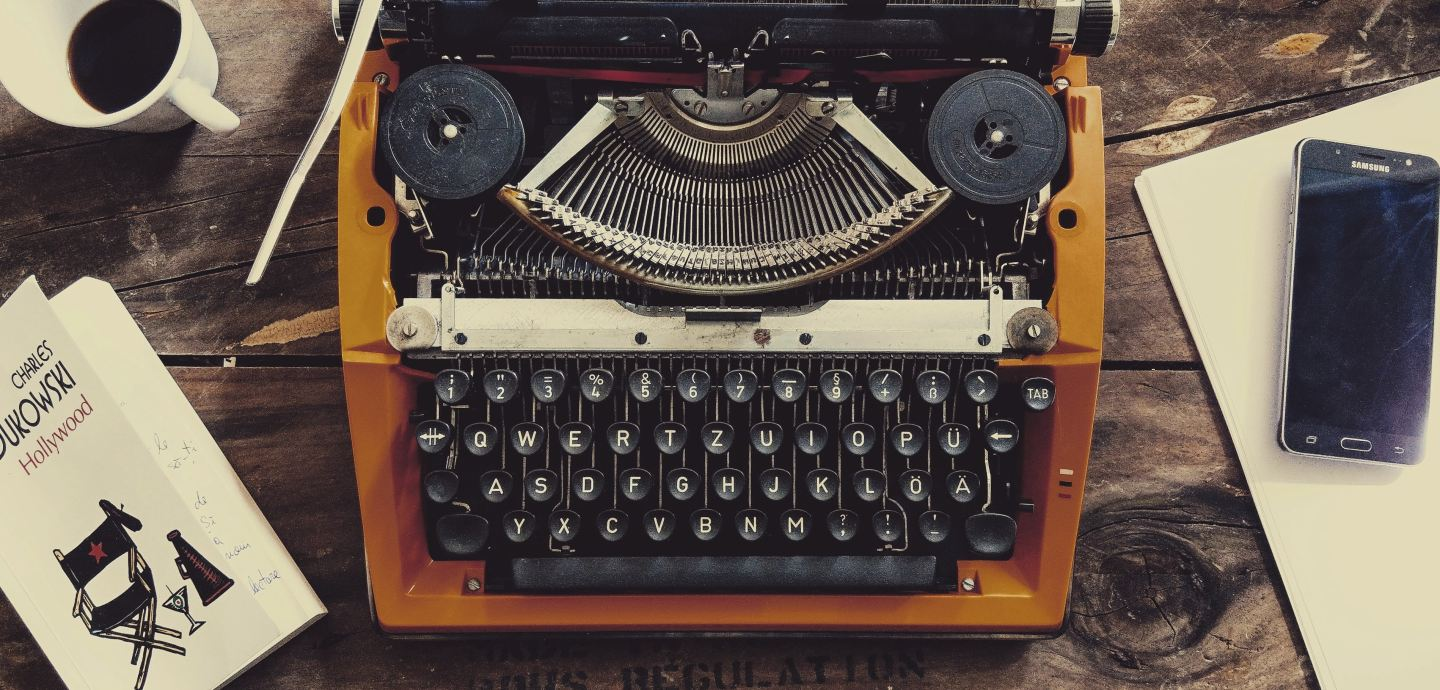 A photograph of a typewriter on a wood table