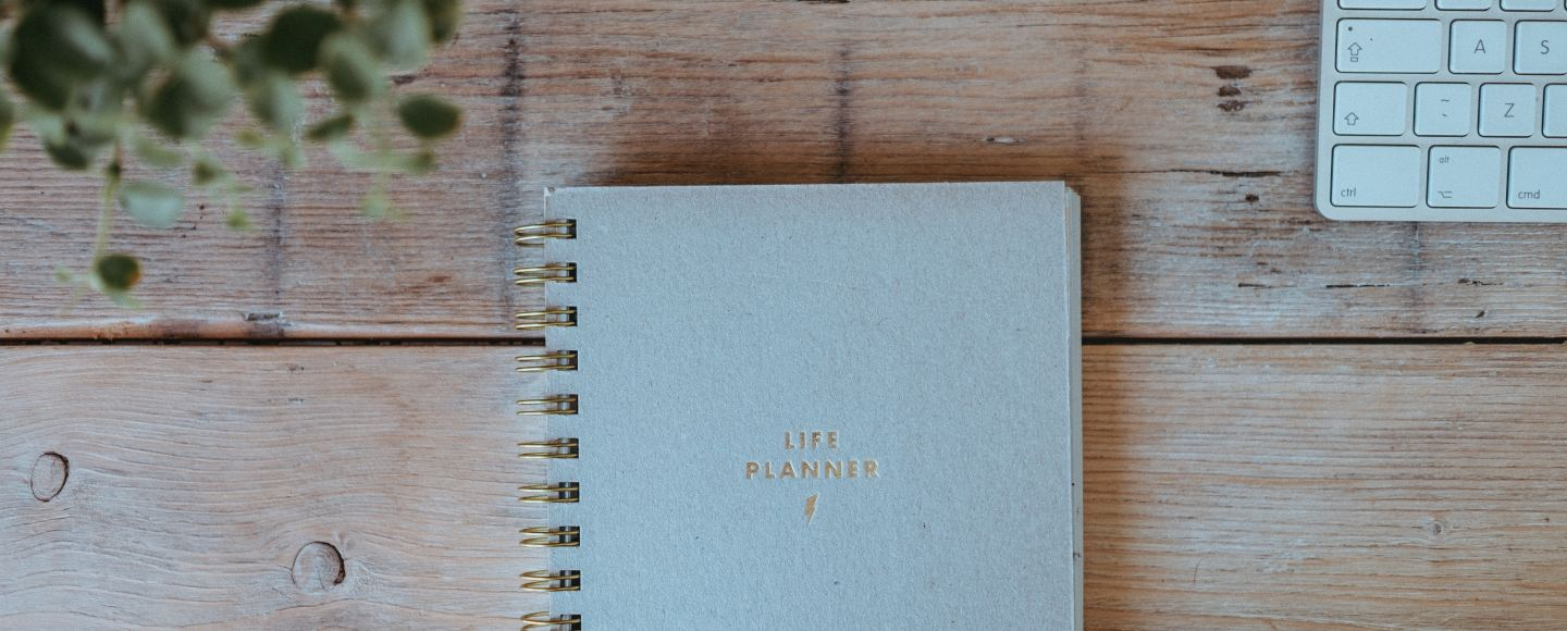 "A picture of a desk with a notebook that says ""Life Planner"""