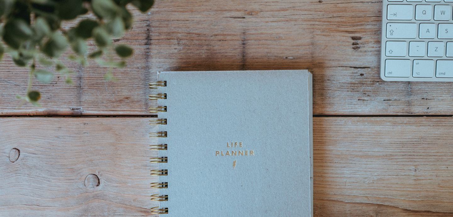 """A picture of a desk with a notebook that says """"Life Planner"""""""