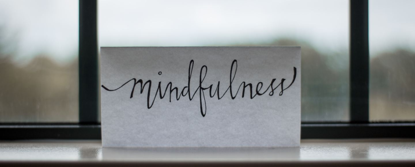 "A piece of paper next to a window with ""Mindfulness"" written on the piece of paper"