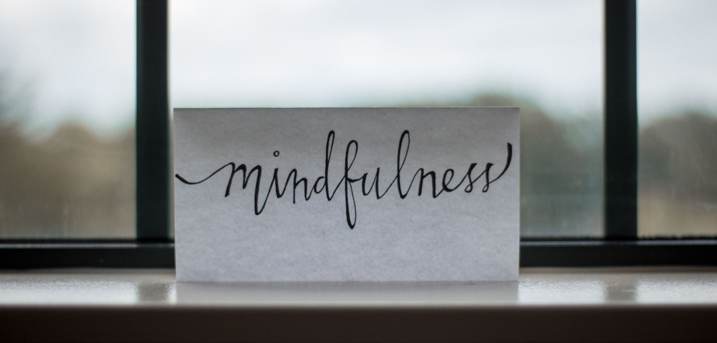 """A piece of paper next to a window with """"Mindfulness"""" written on the piece of paper"""