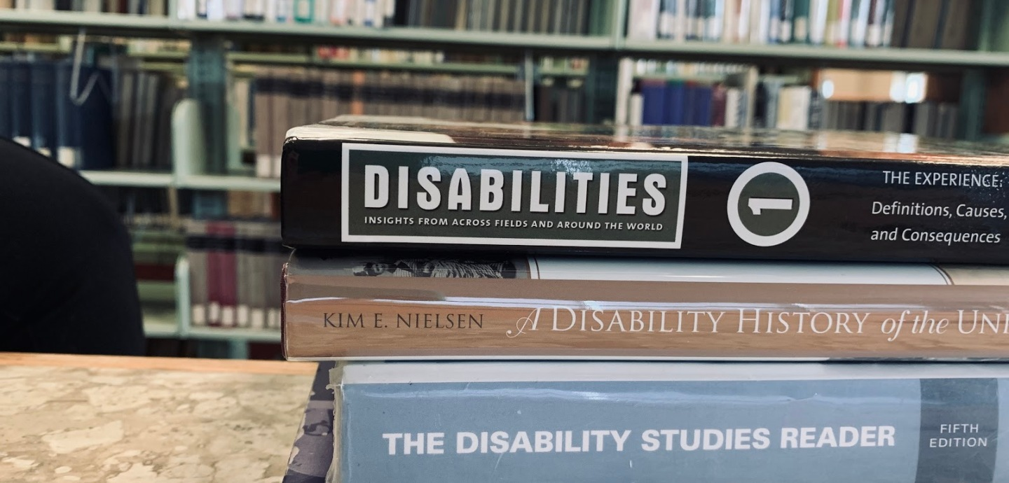 Four texts on disability studies stacked in front of bookshelves