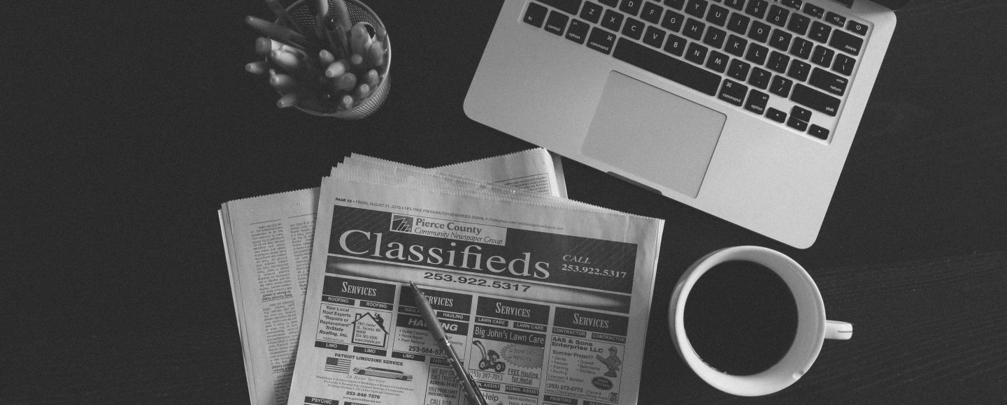 A black and white photo of an open laptop and the classifieds section of a newspaper