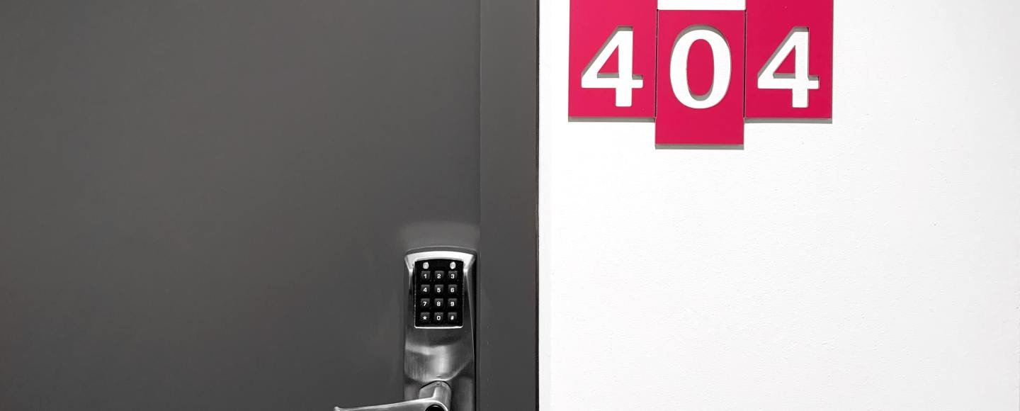 A picture of a closed door with the numbers 404 on the wall to the right of the door handle