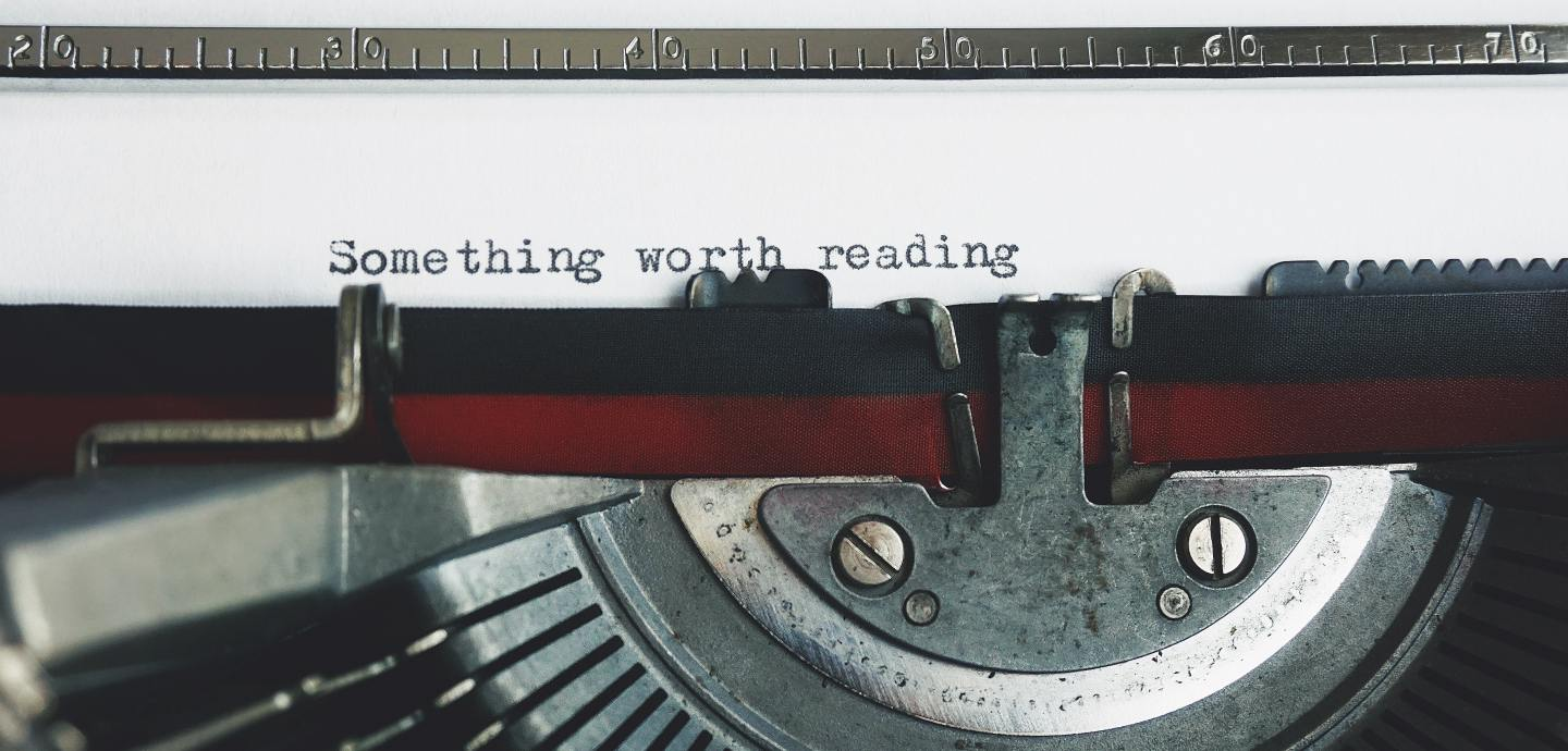 "A close up photograph of a typerwriter which has typed out ""Something worth reading"""