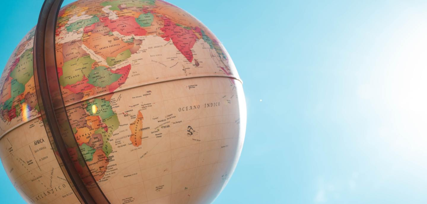 A globe is on the far left hand side of the image and you can see the continent of Africa. Behind this globe is a robin egg blue sky and there is some sun on the right, illuminating the globe every so slightly.